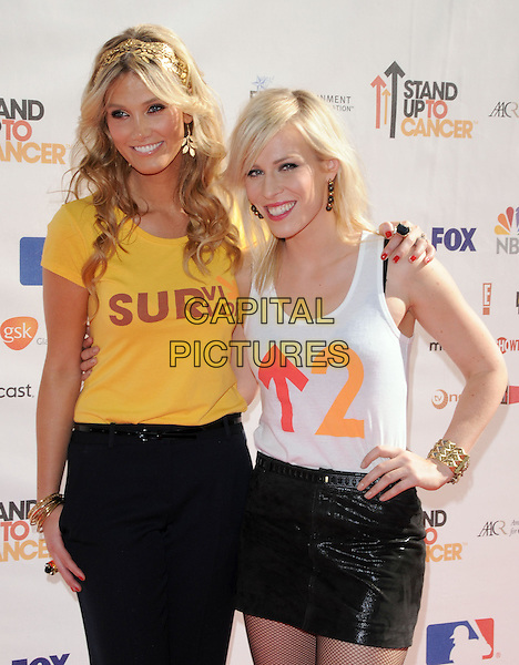 DELTA GOODREM & NATASHA BEDINGFIELD .at Stand Up to Cancer held at Sony Picture Studios in Culver City, California, USA, September 10th 2010.     .half length white vest skirt arm around black  yellow smiling gold hairband hair band earrings make-up wavy hair trousers.CAP/RKE/DVS.©DVS/RockinExposures/Capital Pictures.