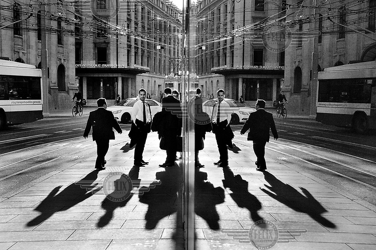 Pedestrains and bank staff are reflected in the windows of one of the many banks lining Rue du Stand, on the edge of the Quartier des Banques.