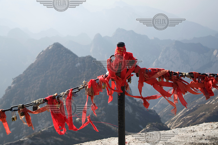 """Prayer ribbons and """"prayer locks"""" attached to a railing on Hua Shan Mountain, a series of granite domes near Xian, that forms one of Taoism's five sacred mountains. Previously a place of retreat and solitude for enlightenment seeking hermits, the spectacular scenery is now often crowded with tourists."""