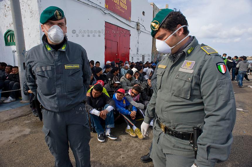 Immigrati Tunisini vengono scortati dalla Guardia di Finanza per l'identificazione prima di essere trasferiti nei centri di accoglienza. Tunisian immigrants are checked by Italian police before boarding a cruise liner to a different part of Italy, on the southern island of Lampedusa.