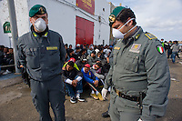 Immigrati Tunisini vengono scortati dalla Guardia di Finanza per l'identificazione prima di essere trasferiti nei centri di accoglienza. Tunisian immigrants are checked by Italian police before boarding a cruise liner to a different part of Italy, on the southern island of Lampedusa.