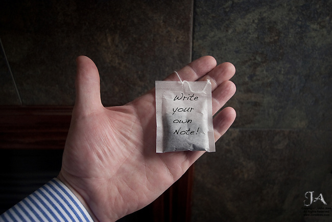 Close up of hand with tea bag with text that says Write your own Note! This is inspiration for using shot  AresPlainTea-3470.tif nearby.