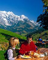 Oesterreich, Herbststimmung im Salzburger Land, Jausenstation vorm Hochkoenig (2.941 m) | Austria, autumn at Salzburger Land, near Dienten, mountain inn and Hochkoenig mountain range (2.941 m), couple having a break, eating
