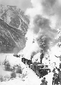 Rotary snowplow train with three engines. There is another train in the near distance with crew cars. A crew of shovelers is breaking up the crust for the rotary.  The letterng on the plow may say D&amp;RG.  If so, it may be #OM judging by the roof lines.<br /> D&amp;RG (?)