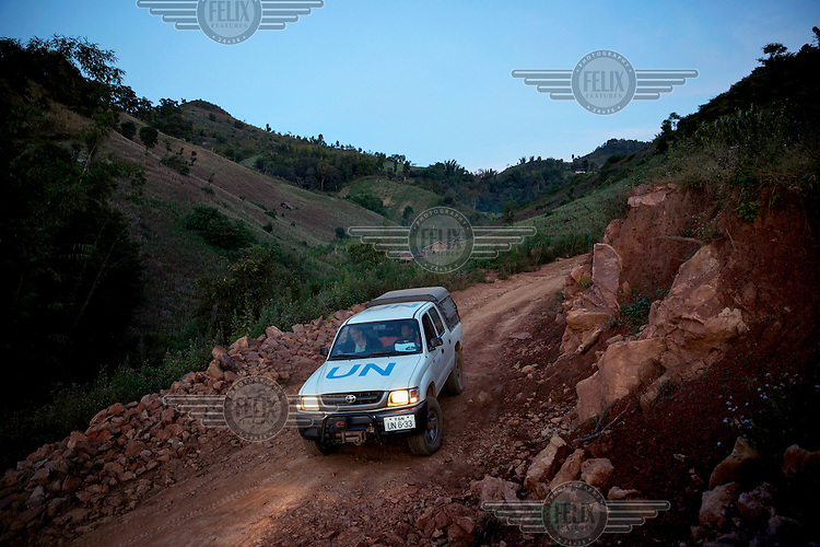 A United Nations Office on Drugs and Crime (UNODC) team drives past poppy fields on a road they built to help villagers access markets in the hope of reducing poppy production, near Long Douay Village in a Shan State Army - South controlled area of Shan State.