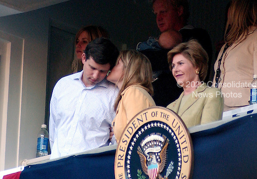 Washington, D.C. - April 14, 2005 -- Jenna Bush, daughter of United States President George W. Bush seems to be whispering something in the ear of Henry Hager in the Presidential Box at RFK Stadium in Washington, D.C. on April 14, 2005.  First lady Laura Bush is a right..Credit: Ron Sachs / CNP.(RESTRICTION: NO New York or New Jersey Newspapers or newspapers within a 75 mile radius of New York City)