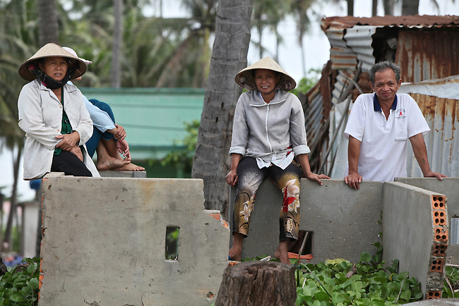 Local residents watch the morning's activities on the beach in Mui Ne, Vietnam. Nov. 20, 2011.