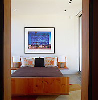 View into a bedroom with a wooden double bed with built-in side tables and a large architectural photograph on the wall