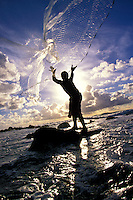 Young local Hawaiian man net fishing of the Kona Coast on the Big Island of Hawaii