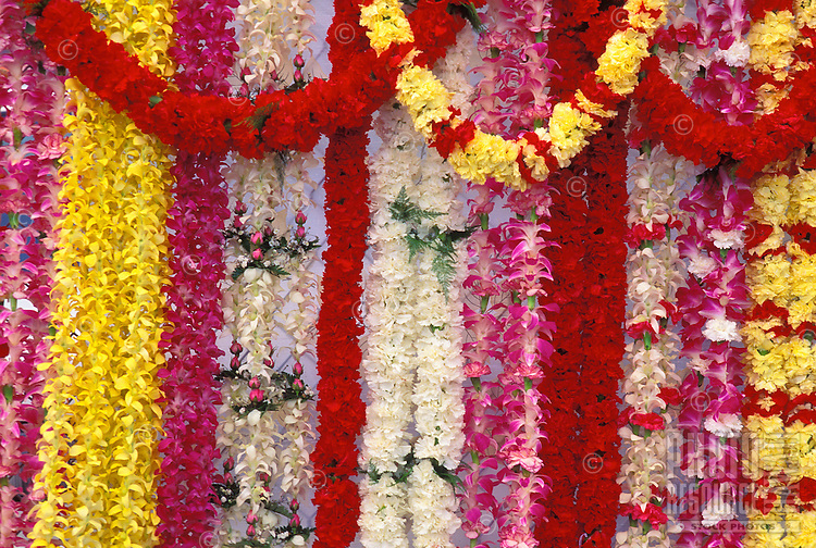 Flower leis of many colors and types hanging at airport lei stands
