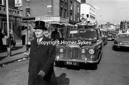 Hoxton funeral east London. Hoxton Street, funeral director in formal top hat walks in front of the heart through Hoxton. 1978.<br />