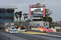 Mar. 10, 2012; Gainesville, FL, USA; NHRA funny car driver Cruz Pedregon (right) races alongside John Force during qualifying for the Gatornationals at Auto Plus Raceway at Gainesville. Mandatory Credit: Mark J. Rebilas-