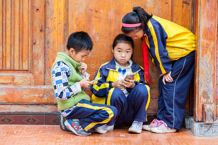 Matang, a Gejia Village in Guizhou, China.  Children Checking their Cell Phones.