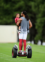 Jul 31, 2009; Flagstaff, AZ, USA; Arizona Cardinals wide receiver Larry Fitzgerald carries his son Devin Fitzgerald as he leaves the field on a segway scooter following training camp on the campus of Northern Arizona University. Mandatory Credit: Mark J. Rebilas-