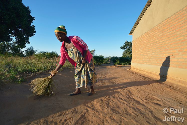Misuzi Tembo sweeps the earth outside her home in Kayeleka Banda, Malawi. Pregnant with her first child, she receives support from the Maternal, Newborn and Child Health program of the Livingstonia Synod of the Church of Central Africa Presbyterian. Tembo's husband has a job in South Africa and sends home money to support her.