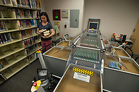 NWA Democrat-Gazette/J.T. WAMPLER Gina Pulciani, circulation clerk at the Springdale Public Library, unloads books from the library's book sorting machine Monday March 5, 2018. The machine is in need of replacing since it is hard to find parts for repairs and requires near constant oversight by staff members.