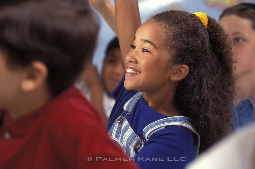 Black girl raising her hand in a middle school classroom