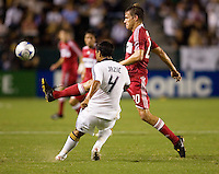 Chicago Fire forward Brian McBride (20) sends a ball past LA Galaxy defender Ante Jazic (4) during a MLS match. The Chicago Fire defeated the LA Galaxy 1-0 at Home Depot Center stadium in Carson, California on Thursday, August 21, 2008.