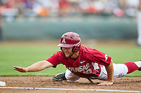 Arkansas Razorbacks outfielder Joe Serrano (10) dives back to first base against the Virginia Cavaliers in Game 1 of the NCAA College World Series on June 13, 2015 at TD Ameritrade Park in Omaha, Nebraska. Virginia defeated Arkansas 5-3. (Andrew Woolley/Four Seam Images)