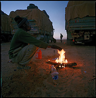 Sahara desert, Libya-Chad, November/December 2004..Every week, a convoy of 40 privately owned Libyan trucks loaded by the WFP with about 1000 metric tons of western food aid cross 2500 km of deep desert across Libya and Chad to reach more than 200 000 refugees from Darfur in camps near the Sudanese border. Warming up after a very cold night outside...
