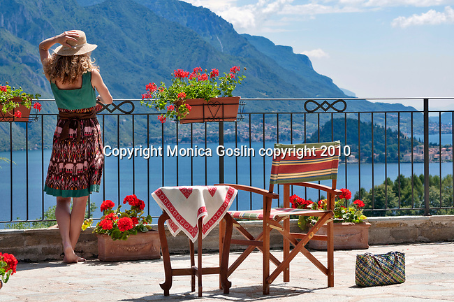 A girl wearing a straw hat, admires the view of Lake Como, Italy from a terrace in Menaggio with the town of Bellagio in the background