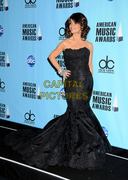 PAULA ABDUL .At the 2009 American Music Awards - Press Room held at the Nokia Theatre L.A. Live, Los Angeles, California, USA, .22nd November 2009..AMA AMAs full length strapless black dress fishtail gown hand on hip silver diamante bracelets tassels long maxi .CAP/ADM/BP.©Byron Purvis/AdMedia/Capital Pictures.