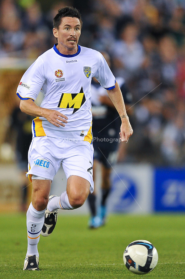 MELBOURNE, AUSTRALIA - NOVEMBER 28, 2009: Steve Fitzsimmons from Gold Coast runs with the ball in round 16 of the A-league match between Melbourne Victory and Gold Coast United at Etihad Stadium on November 28, 2009 in Melbourne, Australia. Photo Sydney Low www.syd-low.com
