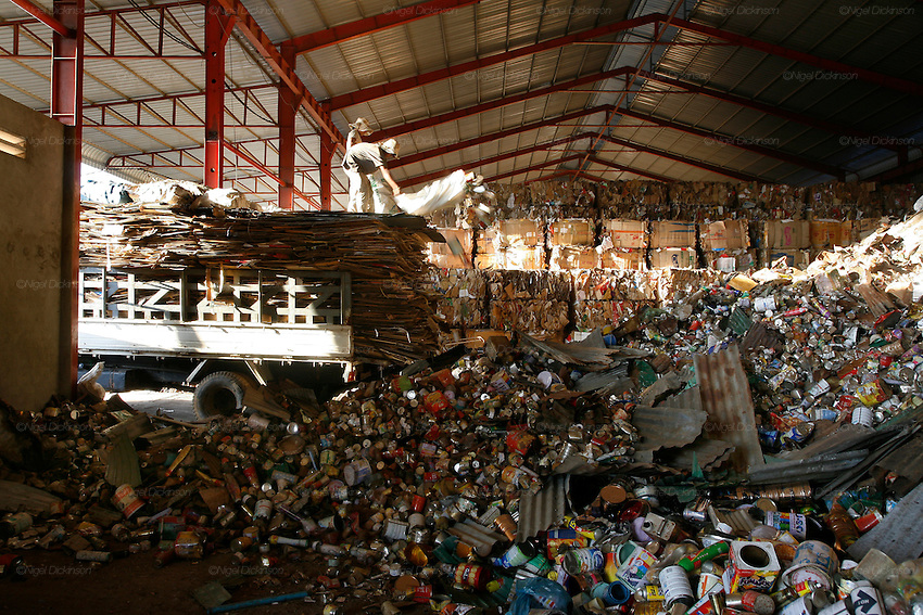 A truck brings metal cans to the recycling warehouse, which operates big distribution for aluminium cans, and general metals, on the edge of Phnom Penh. Aluminium cans are sold with a street value of about 1$ the kilo, the small warehouse add 10% and all the cans are shipped. already sorted to the big distribution recycling warehouses outside Phnom Penh. Here the aluminium cans are squashed into bricks and stacked or placed in mountains for export to Thailand and Vietnam for truning back into the raw material.