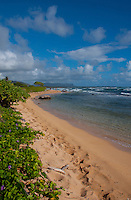 Morning walkers leave behind a trail of footprints along this picturesque, soft sand beach fronting the Kauai Beach Resort on the East side of Kauai.