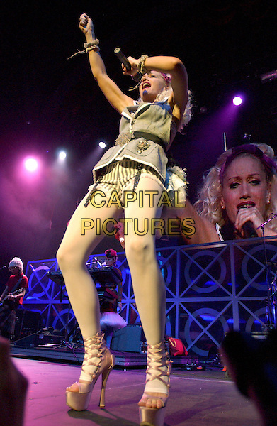 GWEN STEFANI.performs live at The 2004 KROQ Almost Acoustic Christmas Concert, Night One, held at The Universal Ampitheatre in Universal City, California, USA,.December 11th 2004..full length concert live gig music stage white tights alice band waistcoat dress brooch broach belt platform shoes open toe  strappy high heels.Ref: DVS.www.capitalpictures.com.sales@capitalpictures.com.©Capital Pictures.