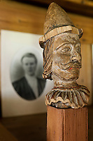 Close up of a wooden newel post which has been carved into a head