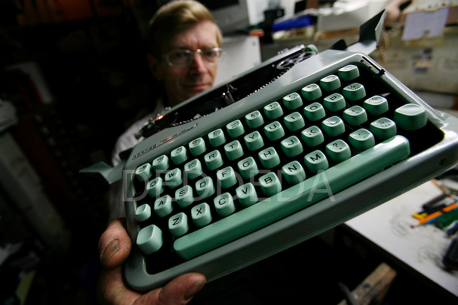 """Jes Vowles, the last typewriter repairman to be found in the Victoria Yellow Pages, inspects a vintage portable Hermes Baby typewriter, possibly made in the 1950's or 1960's, at his Type """"n"""" Write Shop in Victoria, British Columbia. Photo assignment for the Globe and Mail national newspaper in Canada."""