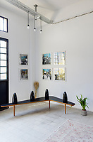 """A converted shoe factory blends old world flavour with warehouse edge. On the Boomerang Table by XXe Siecle, """"Yara, Maya, Zeina, Racha"""" Burqa dolls by Carlo Massoud. Silkscreens are by Alfred Tarazi"""