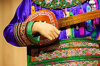 Zhaoxing, Guizhou, China.  Young Woman of the Dong Ethnic Minority Playing a Pipa, a Five-stringed Lute.