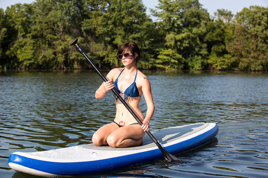 A beautiful smiling woman on Lady Bird Town Lake Austin with SUP paddle board on a hot summer's day. Austin, Texas.