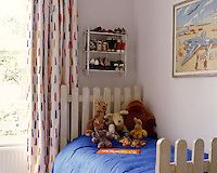 Detail of a child's bed with headboard and footboard designed to resemble picket fencing