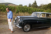 Italy. Tuscany. Villa A Sesta is part of the village Castelnuovo. Riccardo Tattoni stands in front of his vintage Bentley Station Wagon S2 (1961) and near a vineyard belonging to the Agricola Tattoni Villa A Sesta. A vineyard is a plantation of grape-bearing vines, grown mainly for winemaking, but also raisins, table grapes and non-alcoholic grape juice. 18.09.10 © 2010 Didier Ruef