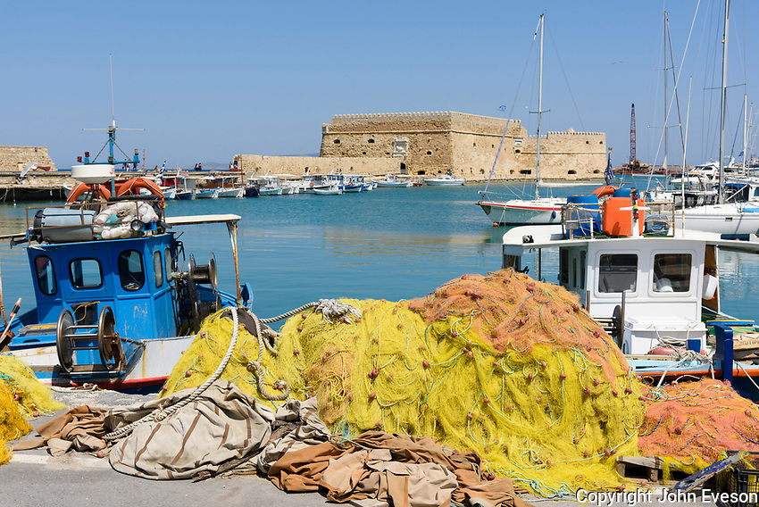 Fishing boats in the port at Heraklion, with  the fortress of Rocca al Mare, island of Crete, Greece.