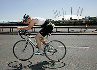 04 AUG 2007 - LONDON, UK - An age group competitor cycles past the Millenium Dome - London Triathlon. (PHOTO (C) NIGEL FARROW)