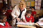 K-8 Parochial School Bronx New York Grade 3 mathematics lesson on measurement using rulers horizontal female teacher checking student's work horizontal