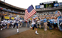 North Carolina safety Matt Merletti (25) carries an American flag onto the field during the Meineke Car Care Bowl college football game at Bank of America Stadium in Charlotte, NC.