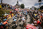 The peloton climb the Muur Kapelmuur in Geraardsbergen during Stage 1 of the 2019 Tour de France running 194.5km from Brussels to Brussels, Belgium. 6th July 2019.<br /> Picture: ASO/Pauline Ballet | Cyclefile<br /> All photos usage must carry mandatory copyright credit (© Cyclefile | ASO/Pauline Ballet)