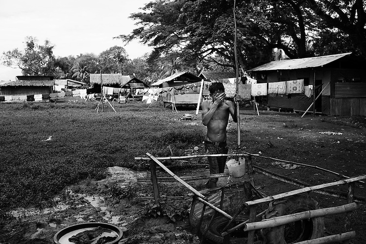 Beyond the Bullets - Washing - ..A young man bathes from one of the three wells that serve the 2,825 people living at the Notre Dame of Dalawan school in the town of Datu Piang on April 22, 2009.  With peace talks at a standstill and increasing military activity, the evacuation center is constantly swelling, with many of its residents having been there for nearly a year and more moving in daily.