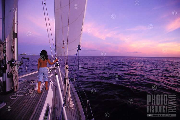 Young girl at sunset on sailboat off Makua Beach, West Side Oahu