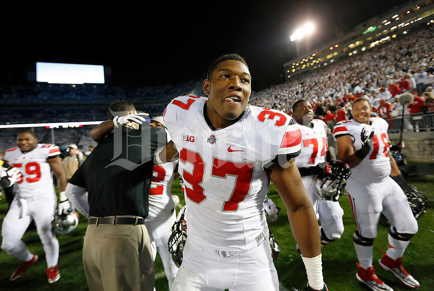 Ohio State Buckeyes linebacker Joshua Perry (37) smiles after being congratulated by asst. coach Luke Fickell following the second overtime of the NCAA Division I football game at Beaver Stadium in University Park, PA on October 25, 2014. (Columbus Dispatch photo by Jonathan Quilter)