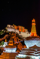 The Potala Palace with stupas in the foreground illuminated at night, Lhasa, Tibet (Xizang), China.