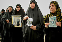 Iraqi women show pictures of relatives detaned in the prison of Abu Graib in Baghdad on MAy 28 2004. in the same day 400 prisoners will be released.