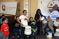 (171126RREI2137) Anna on drum. Many Languages One Voice,  MLOV,  Holiday Celebration and Immigrant Legal Rights Workshop in La Casa, Mt. Pleasant. MLOV is on the same block as La Esquina where Latinos have gathered for decades at the corner of Mt. Pleasant St. and Kenyon St. NW. to play chekers (damas). Washington DC.  Nov. 26 ,2017 . ©  Rick Reinhard  2017     email   rick@rickreinhard.com