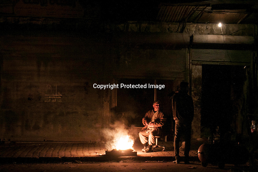 In this Sunday, Dec. 09, 2012 photo, night falls as men warm themselves by fire in a Syrian rebel controlled area in where residents are trying to get back to their daily lives after months of heavy fighting in Aleppo, Syria. (AP Photo/Narciso Contreras)