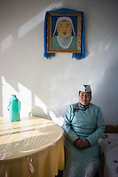 Mongolian herder Renqima wears national costume and poses underneath a portrait of Genghis Khan before she headed for the traditional festival of Naadam in Damao Banner, Inner Mongolia, China, October 2014.